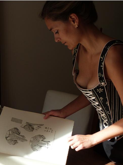 "Model Claudia im barockkorsett von beata Sievi schaut das Buch ""Le corset"" an."