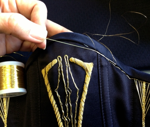 Adding a gold-thread to embellisch the edge of the corset